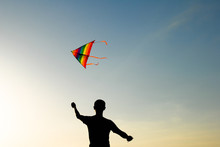Silhouette Of Active Young Man Manipulating Colorful Kite Flying In Air At Summer Sunset