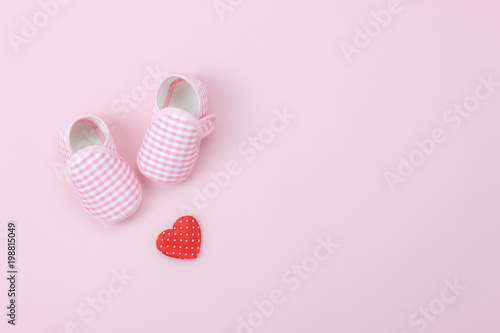 Table top view aerial image of decoration Happy mother's day holiday background concept.Flat lay red heart & baby shoes on modern beautiful pink paper at home office desk.Design pastel tone and space.