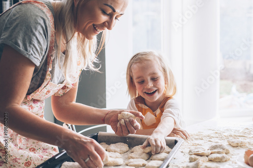 Foto op Plexiglas Koken Mom cooking with daughter on the kitchen