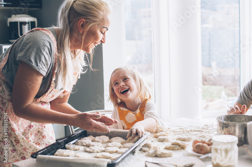 Fotobehang Koken Mom cooking with daughter on the kitchen