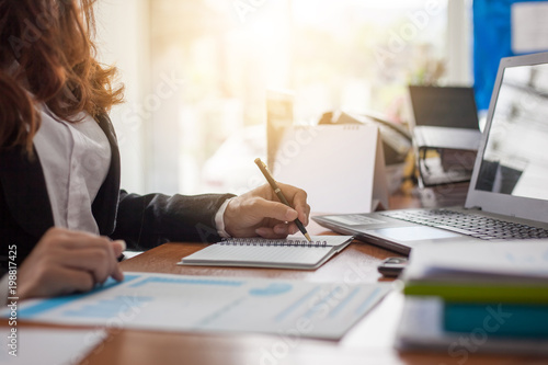 Fotomural  Business woman at working with financial reports and laptop computer in the offi