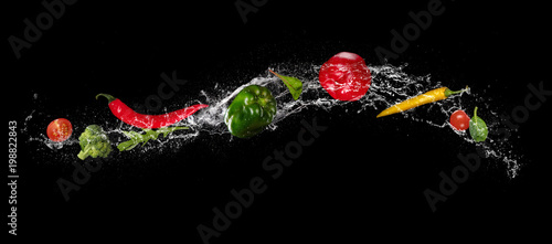 Poster Fresh vegetables Mix of vegetable in water splash on black background.