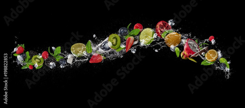 Fotografia  Pieces of fruit in water splash, isolated on black background