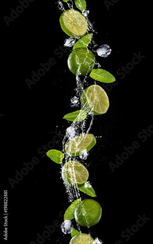 Slices of lime falling in water splash on black background