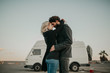Cool young couple kissing each other outdoors while they are embraced, during a road trip stop, with their van in the background.