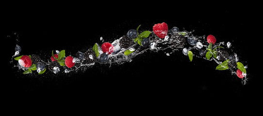 FototapetaMix of berry fruit in water splash, isolated on black background