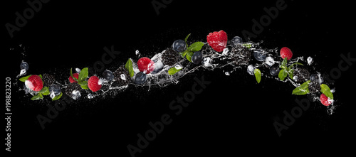 Mix of berry fruit in water splash, isolated on black background