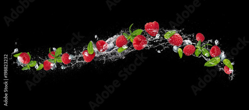 Raspberries falling in water splash on black background
