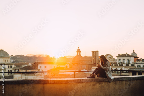 Photo Young girl who uses her cell phone on the roof during the sunset