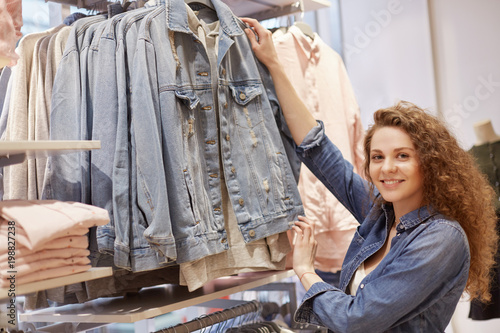 1c82f02e54d Horizontal shot of beautiful young woman with curly hair, pleased  expression, chooses new denim