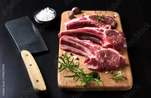 Raw lamb chops on a wooden cutting board with spices on a dark wooden background