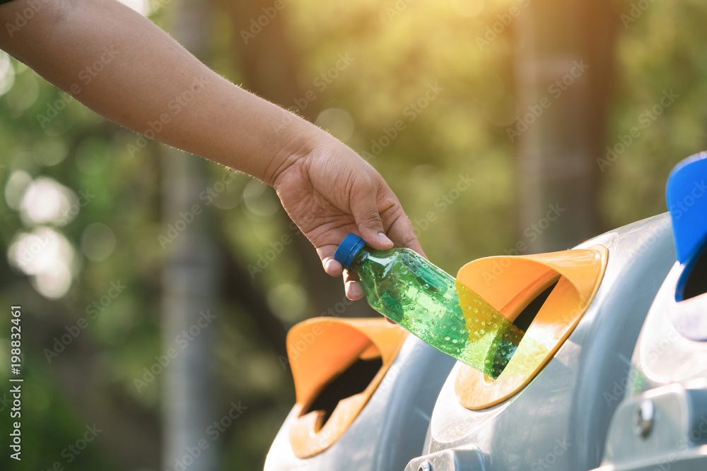 Fototapety, obrazy: Close up hand throwing empty plastic bottle into the trash