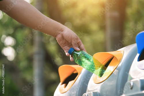 Fotografia, Obraz  Close up hand throwing empty plastic bottle into the trash