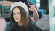 Hairstylist creating a hairstyle for beautyful woman