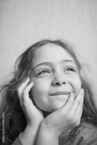 Portrait of a little girl with admiration watching and holding her face with her Canvas Print