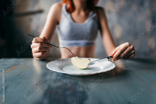 Female person against plate with a slice of apple Wallpaper Mural