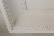 Ornamental White Molding Decor On Ceiling Of White Room Close-up Detail. Interior Renovation And Construction Concept.