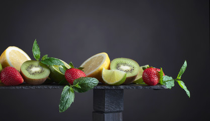 Various fresh summer fruits on black background.