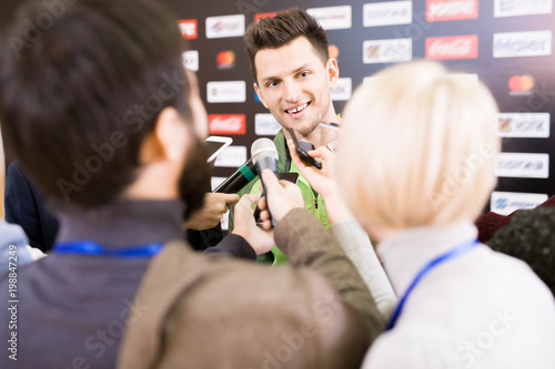 Cheerful young gold medalist of Olympic Games standing against press wall and answering questions of journalists, portrait shot