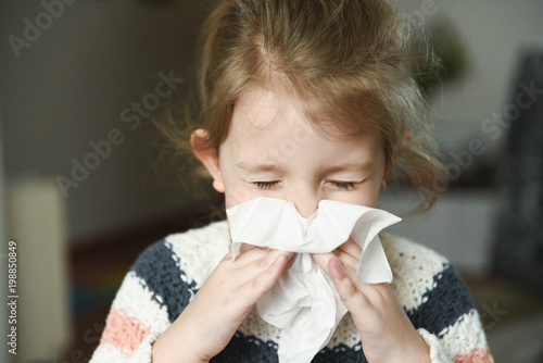 Sick little girl blowing her nose and covering it with handkerchief with eyes cl Fototapet