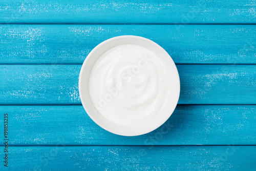 Diet greek yogurt in bowl on rustic wooden table top view.