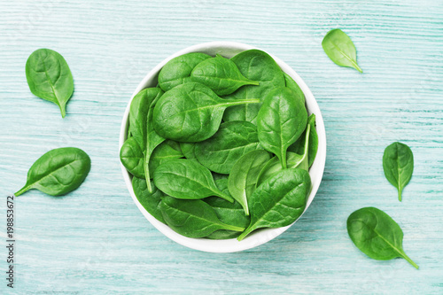 Fresh spinach leaves in bowl on table top view. Organic food.