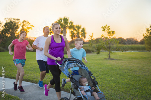 Photo  Beautiful, fit young family walking and jogging together outdoors along a paved
