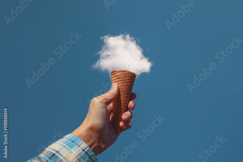 Fotografie, Obraz  hand holding a sugar cone in front of a fluffy white cloud toned with a retro vi