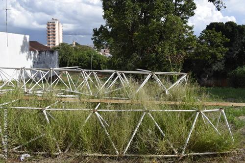 Fotografie, Obraz  Estruturas metálicas treliçadas triangulares abandonada em lote vazio e cercado
