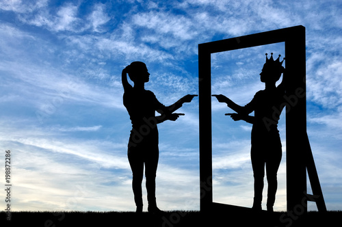 Fototapeta A silhouette of a narcissistic woman raises her self-esteem in front of a mirror