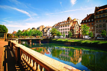 Beautiful Embankment With A Bridge And A Green Garden And Wonderful European Houses And Chalets In The City Of Strasbourg In France