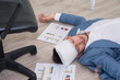 Sick businessman sleeping on floor while using laptop to work hard at office