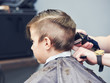 Barber is shaving a hair to Caucasian boy in barbershop.