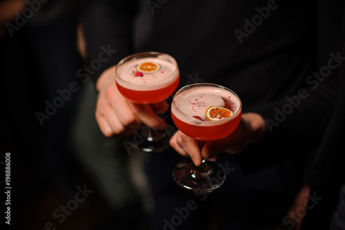 Two people holding cocktail glasses with sweet alcoholic drink