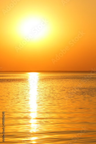 Spoed Foto op Canvas Zee zonsondergang Orange sun over the sea horizon, beautiful sunset, copy space, landscape with a big sun, bloody horizon above the water surface, blank for the designer, orange pattern