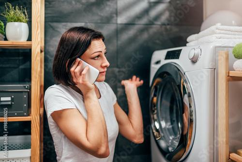 Woman calling for appliance repair service Wallpaper Mural