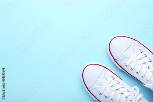 Pair of white sneakers on blue background Fototapeta