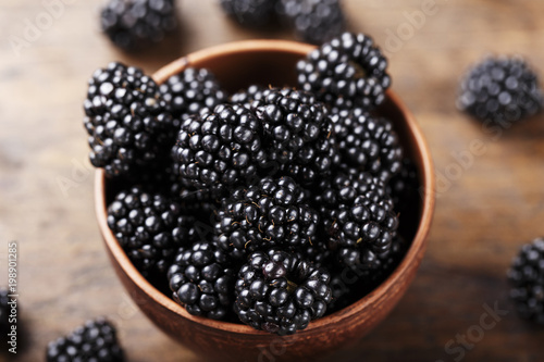 Fotografija  Blackberry on a wooden background. space for text. top view
