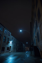 Dark Foggy Urban City Alley At Night After A Rain With Vintage Warehouses