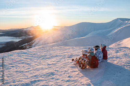 fototapeta na drzwi i meble Group of friends enjoying the beauty of sunset at snowy ski resort. Winter vacation