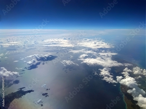 high altitude image of the earth with blue sky and white clouds over the sea wit Canvas Print