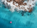 Aerial view of young woman swimming on the pink swim ring in the transparent turquoise sea in Oludeniz. Summer seascape with girl, beach, beautiful waves, blue water at sunset. Top view from drone - 198910660