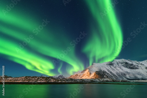 Photo sur Toile Aurore polaire Aurora borealis. Lofoten islands, Norway. Aurora. Green northern lights. Starry sky with polar lights. Night winter landscape with aurora, sea with sky reflection and snowy mountains. Nature. Travel