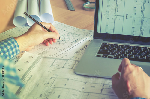 Architect or engineer working in office on blueprint Canvas Print
