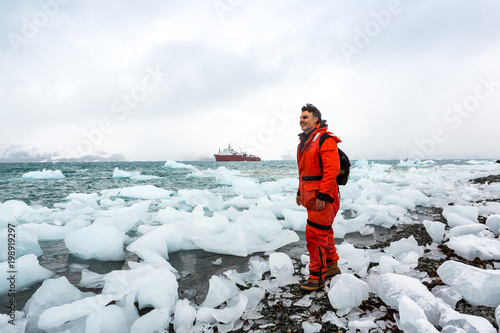 plakat Man walks through ice and snow in Antarctica. Icebergs and everything frozen around you. Cold.