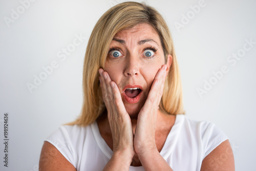 fc41f6c7904f Shocked mature Caucasian woman with open mouth covering cheeks with hands.  Client discovering losses caused