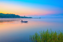 Red Canoe On A Lake At Sunrise