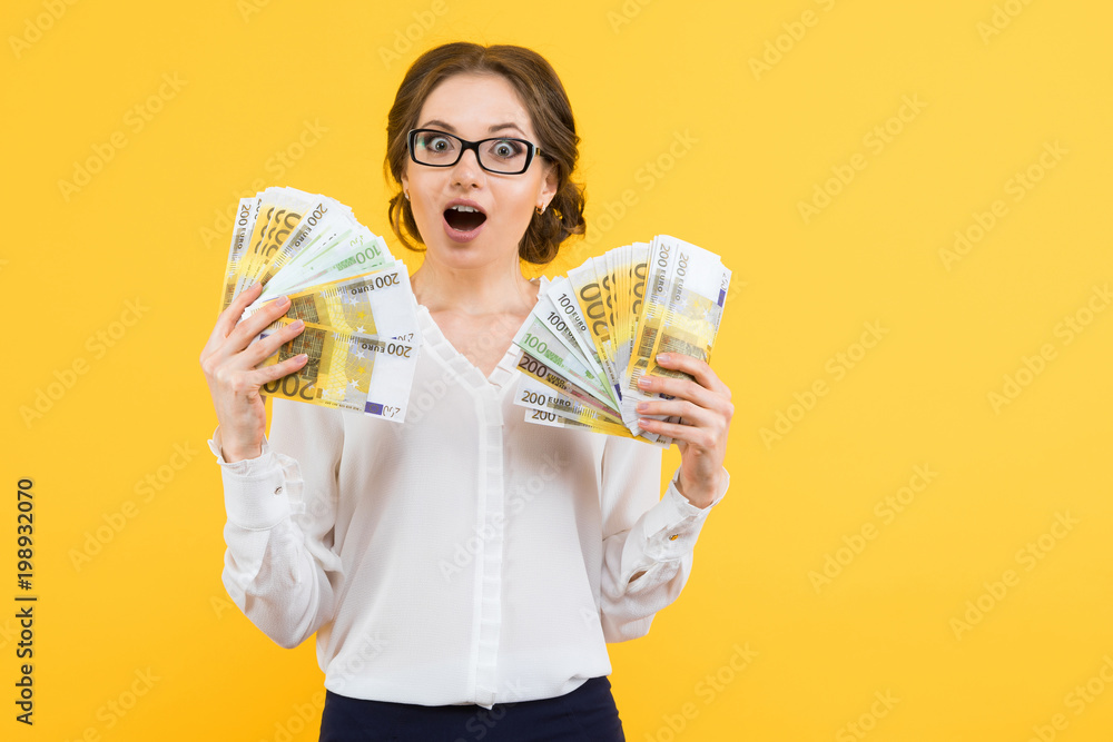 Fototapeta Portrait of confident beautiful happy young business woman with money in her hands standing on yellow background