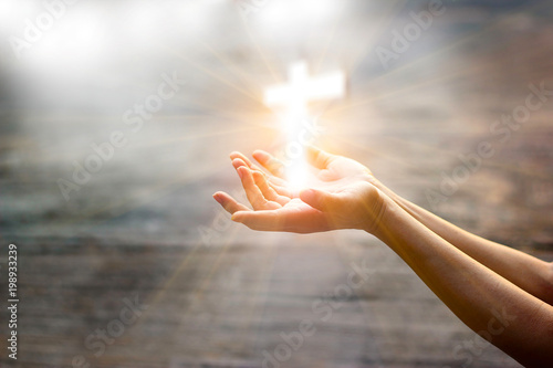 Photo Woman with white cross in hands praying for blessing from god on sunlight backgr