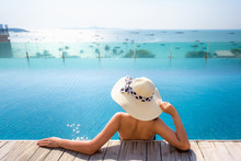 Sexy Woman In Swimsuit Is Relaxing In Swimming Pool, Beautiful Asian Woman Wearing Straw Hat And Relax Sunbathe In Poolside On Summer Holiday At Resort Hotel, Leisure Activities And Relaxation Time